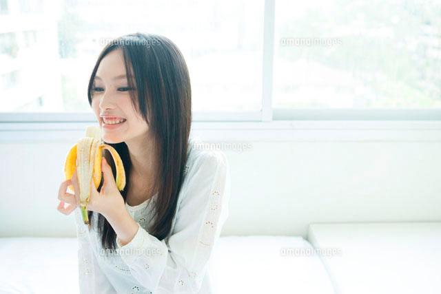 部屋でくつろぎバナナを食べる10代女性[10161000893]  写真素材 ...