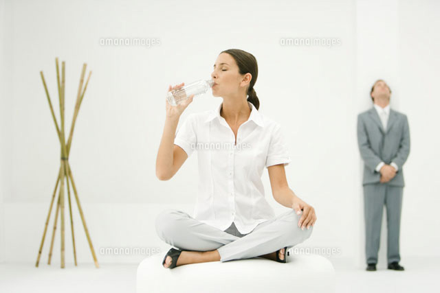 Woman sitting on ottoman drinking from water bottle for Ottoman to sit on
