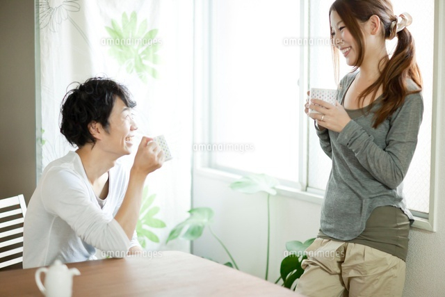 会話しながら笑顔でコーヒーを飲む若い夫婦[10367002700]| 写真 ...